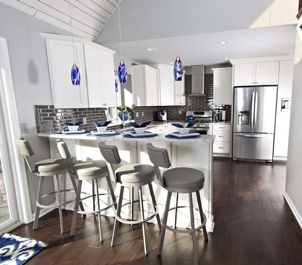 Stainless steel appliances, white shaker cabinets, charcoal glass tile, quartz countertops, cobalt blue pendant lighting, dark acacia wood flooring.